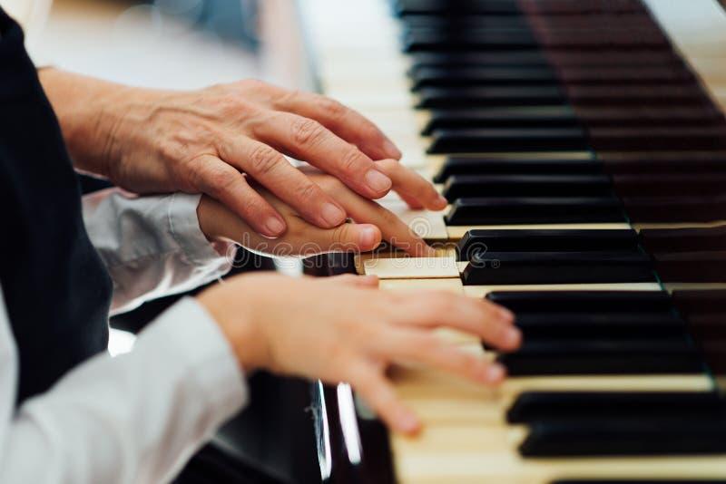 La mano experimentada del viejo profesor de música ayuda al alumno del niño imagen de archivo