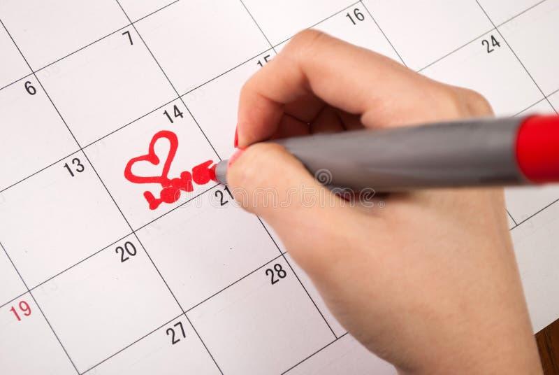 La mano femenina con el corazón del dibujo de lápiz y la palabra aman en el calendario para el día de tarjetas del día de San Val fotos de archivo
