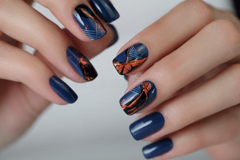 La mano femenina con los clavos brillados azul marino Mano de la muchacha Manicura femenina foto de archivo