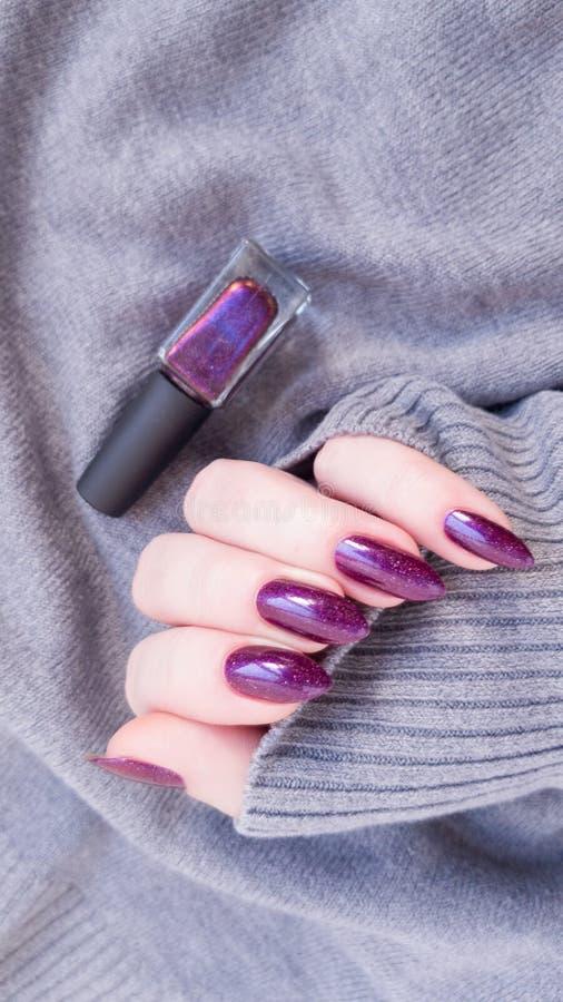 La mano femenina con los clavos largos lleva a cabo un esmalte de uñas de la botella imagen de archivo