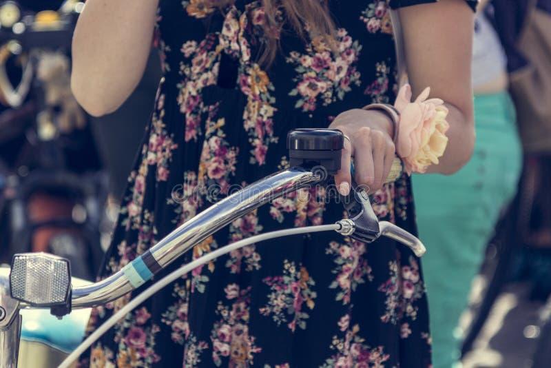 La mano femenina con una flor sostiene el volante de una bicicleta Parte de la imagen foto de archivo