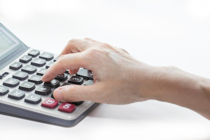 La mano femenina está tocando los botones en la calculadora, cerrado-para arriba y aislado en el fondo blanco imagenes de archivo