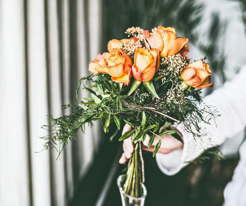 La mano femenina hace las rosas el arreglo del manojo de las flores en el florero de cristal fotografía de archivo