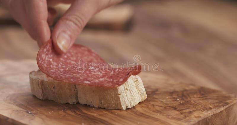 La mano femenina hace la rebanada del baguette del bocadillo con el queso cremoso y el salami fotos de archivo