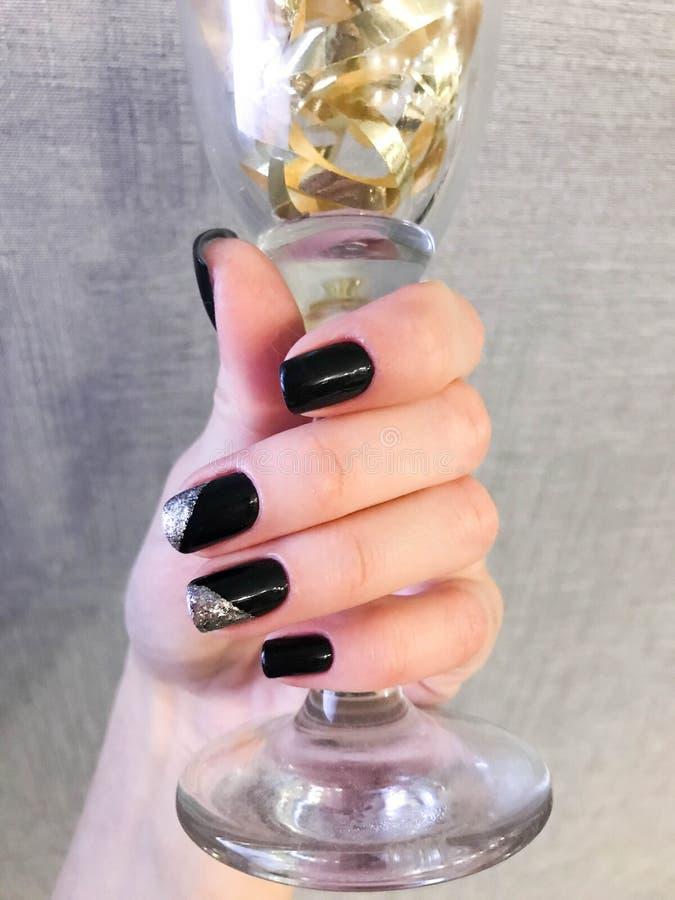 La mano femenina hermosa con los fingeres finos y la manicura negra con el barniz del gel con plata chispea en los clavos que sos imágenes de archivo libres de regalías