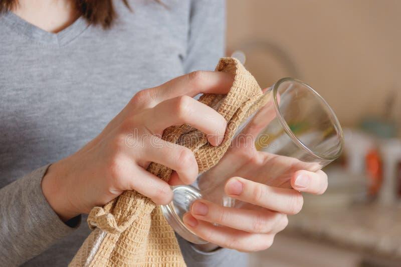 La mano femenina limpia el vidrio limpio por el golpecito en cocina Quehacer doméstico, concepto Spring Cleaning fotografía de archivo