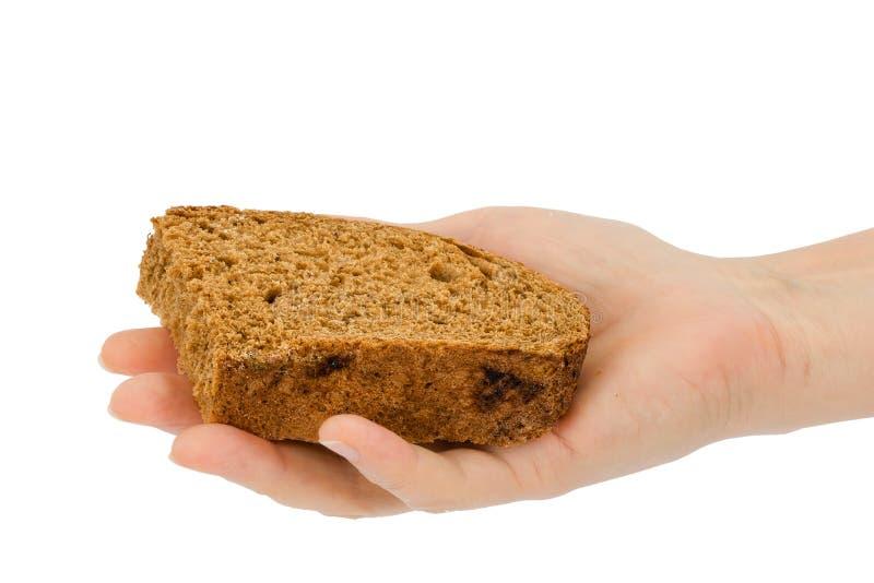 La mano femenina lleva a cabo una rebanada de pan, aislada en el fondo blanco imagen de archivo libre de regalías