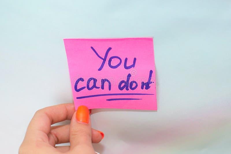 La mano femenina que lleva a cabo una etiqueta engomada rosada que le diga puede hacerla en un fondo azul imagenes de archivo