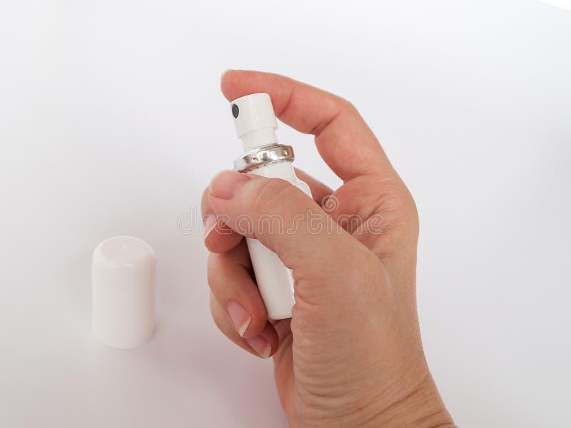 La mano femenina que sostiene el aerosol médico blanco puede cerrarse para arriba Droga bajo la forma de espray imagen de archivo