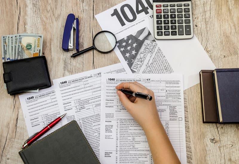 La mano femenina rellena los impresos 1040 de impuesto en una tabla de madera imagen de archivo