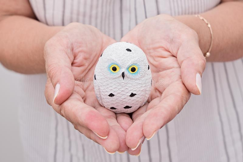 La mano femenina sostiene el pequeño búho de cerámica en palma foto de archivo libre de regalías