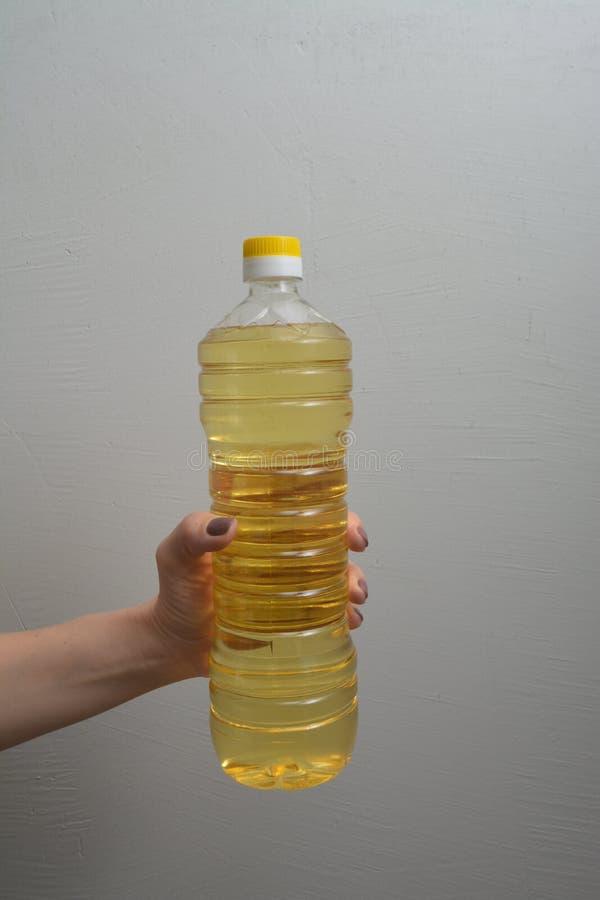 La mano femenina sostiene la botella del aceite vegetal imágenes de archivo libres de regalías