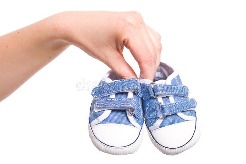 La mano femenina sostiene los pequeños zapatos de bebé, aislados fotos de archivo libres de regalías