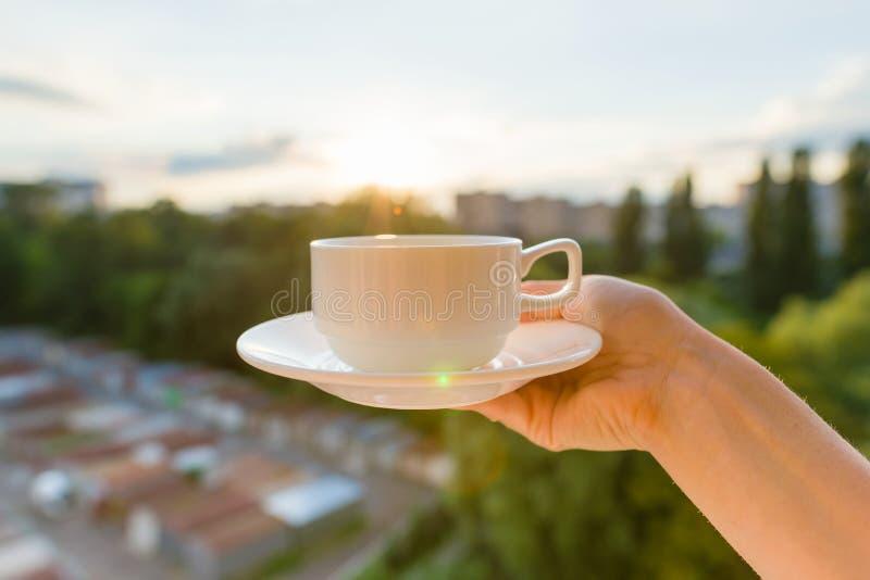 La mano femenina sostiene la taza y el platillo blancos Puesta del sol de la tarde del fondo, silueta de la ciudad imágenes de archivo libres de regalías
