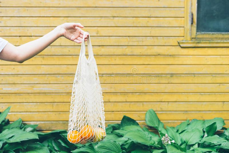 La mano femenina sostiene un bolso de compras del algodón con las naranjas y las manzanas imágenes de archivo libres de regalías