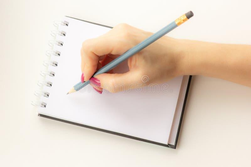 La mano femenina sostiene un lápiz y escribe en un cuaderno Primer fotos de archivo libres de regalías