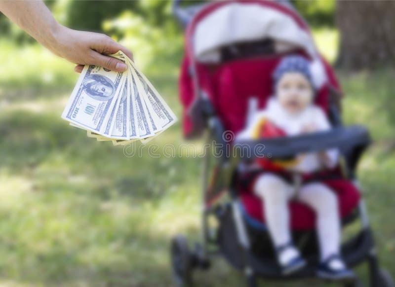 La mano femenina sostiene una fan con los dólares contra un niño en una silla de ruedas, traficando en niños imagenes de archivo