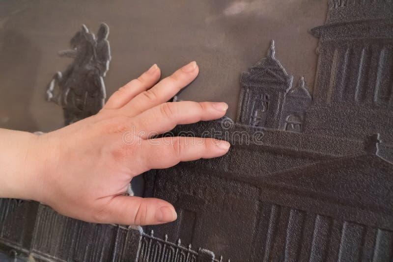 La mano femenina toca un patrón especial en relieve para los discapacitados visuales fotos de archivo