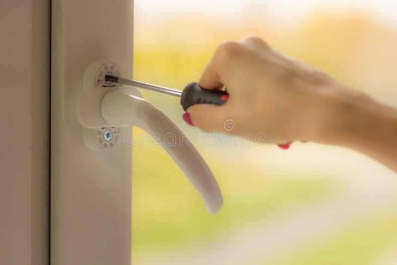 La mano femenina tuerce el tornillo en la ventana con un destornillador fotografía de archivo