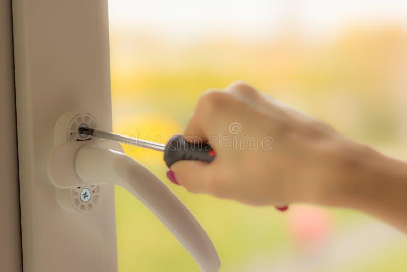 La mano femenina tuerce el tornillo en la ventana con un destornillador, primer foto de archivo