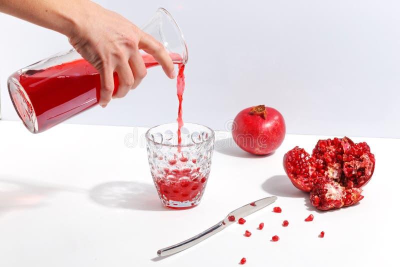 La mano femenina vierte el jugo de la granada en un vidrio Granadas en una tabla blanca foto de archivo