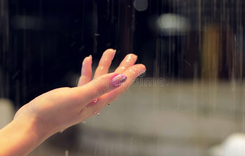 La mano femminile con un bello manicure rosa raggiunge per l'acqua di gocciolamento Acqua della spruzzata Fontana immagini stock