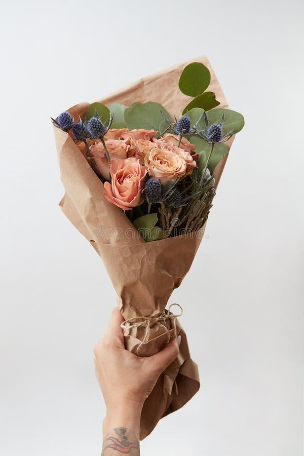 La mano femminile d? il mazzo con le rose di corallo e la foglia verde su fondo leggero, spazio della copia Regalo per il giorno  fotografia stock