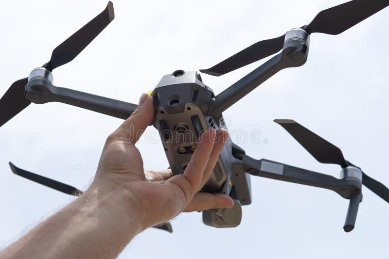 La mano femminile lancia il fuco per il volo, con cui potete prendere le foto e la contaminazione del video, primo piano fotografia stock libera da diritti