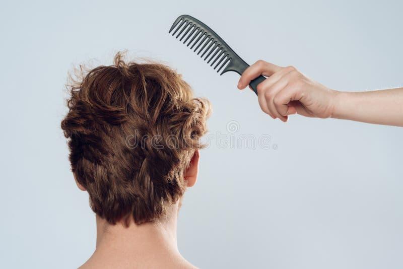 La mano femminile pettina i capelli dell'uomo dai capelli rossi fotografia stock libera da diritti