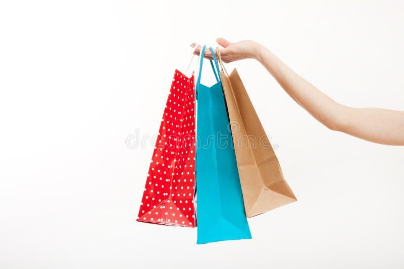 La mano femminile sta tenendo le borse variopinte di compera su fondo bianco Copi lo spazio e derida su Modello e fondo in bianco immagine stock libera da diritti
