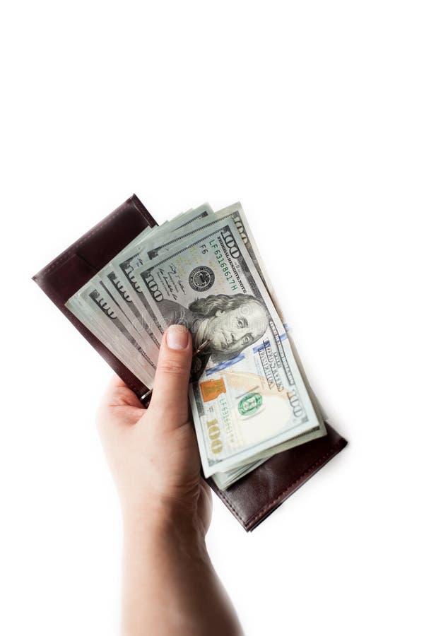 La mano femminile tiene il portafoglio marrone aperto con un batuffolo spesso delle banconote in dollari di nuovo cento Isolato s fotografie stock libere da diritti