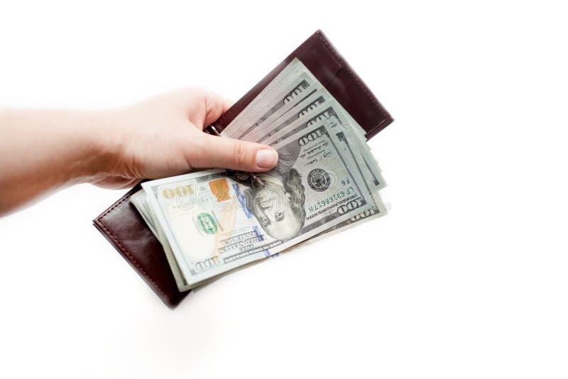 La mano femminile tiene il portafoglio marrone aperto con un batuffolo spesso delle banconote in dollari di nuovo cento Isolato s fotografia stock