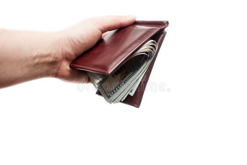 La mano femminile tiene il portafoglio marrone chiuso con un batuffolo spesso di nuove fatture Isolato sopra un fondo bianco fotografia stock libera da diritti