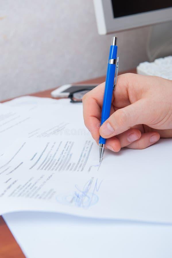 La mano firma i documenti immagini stock