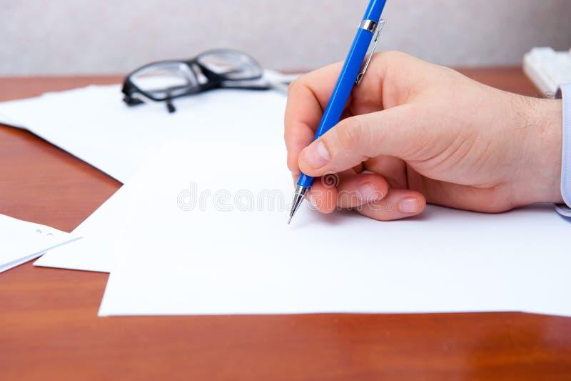 La mano firma i documenti fotografia stock