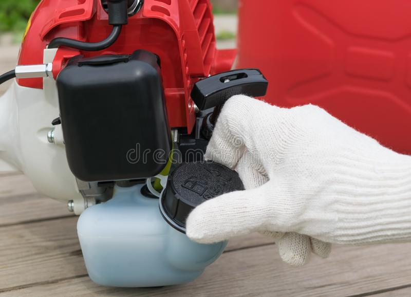 La mano in guanto chiude il carro armato di benzina per la falciatrice da giardino, primo piano fotografia stock libera da diritti