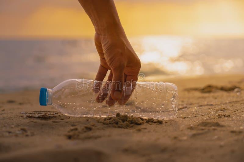 La mano guarda limpieza la botella plástica en la playa en el sc de la puesta del sol foto de archivo