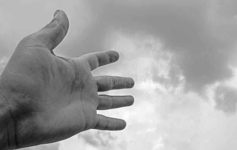 La mano ha allungato ad un cielo riempito di nuvole scure adatto a copertina di libro, illustrazione della carta, presentazione R fotografia stock