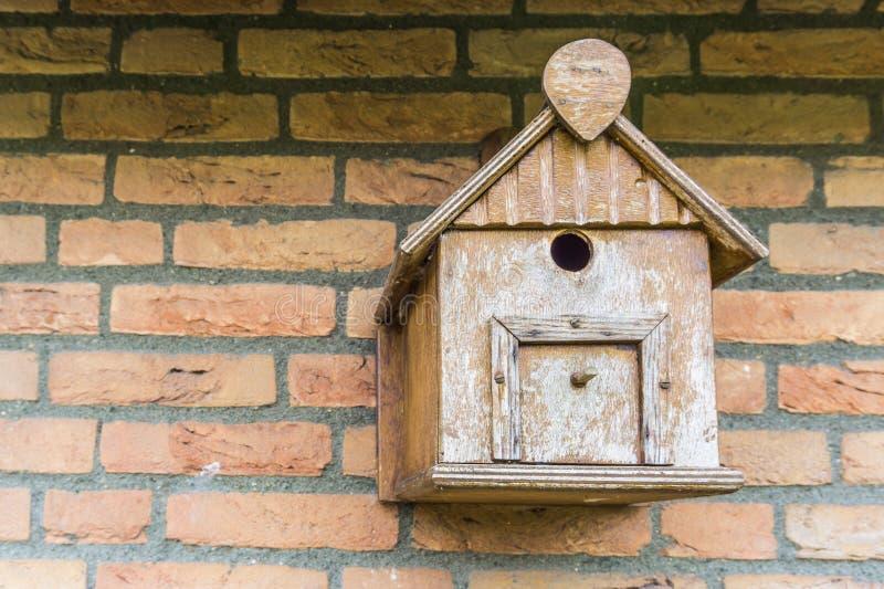 La mano ha elaborato il riparo di legno della casa dell'uccello per gli uccelli che appendono su un muro di mattoni immagini stock libere da diritti