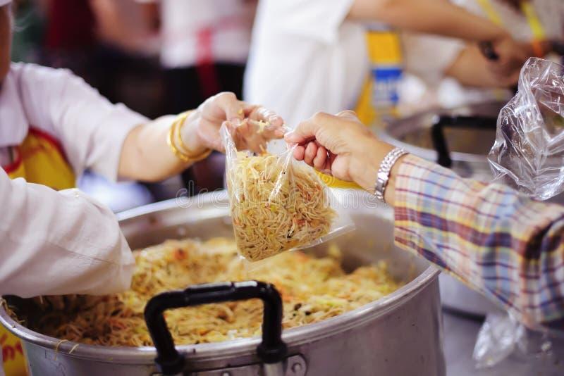 La mano ha offerto donare l'alimento da una parte dell'uomo ricco: Concetti d'alimentazione fotografie stock