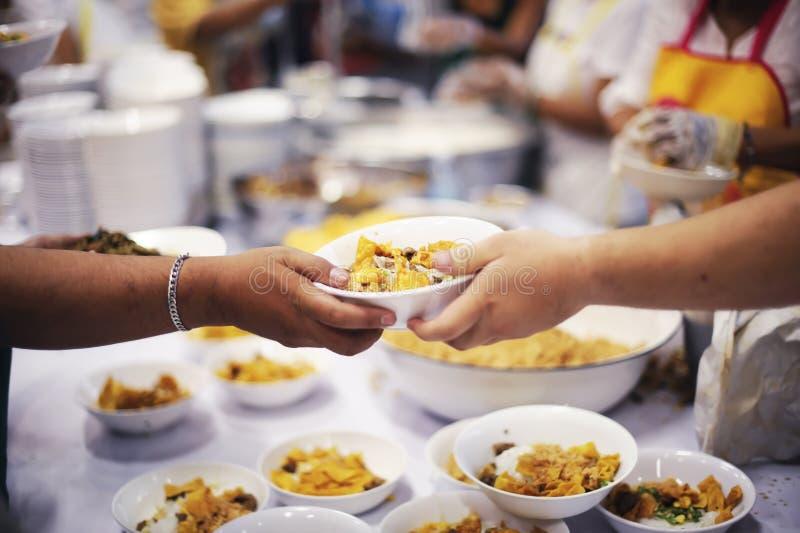 La mano ha offerto donare l'alimento da una parte dell'uomo ricco: Concetti d'alimentazione fotografia stock