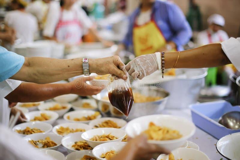 La mano ha offerto donare l'alimento da una parte dell'uomo ricco: Concetti d'alimentazione immagine stock libera da diritti