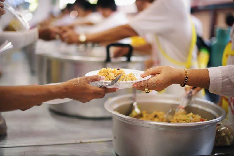 La mano ha offerto donare l'alimento da una parte dell'uomo ricco: Concetti d'alimentazione fotografia stock libera da diritti