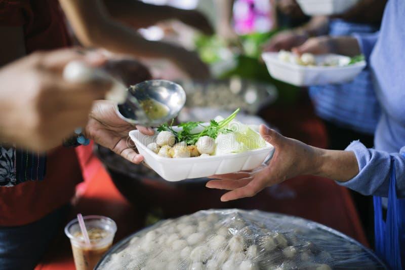 La mano ha offerto donare l'alimento da una parte dell'uomo ricco: Il concetto di divisione sociale: Gente povera che riceve alim fotografie stock