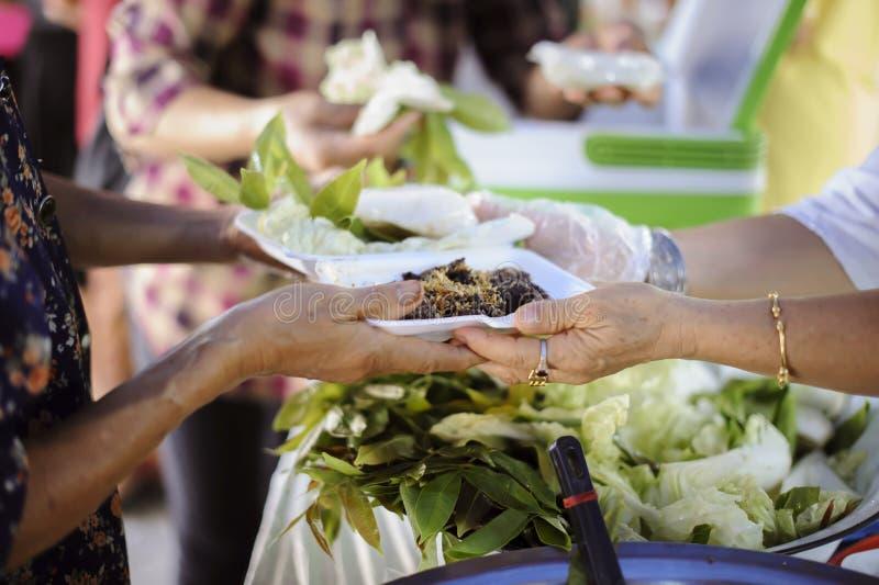 La mano ha offerto donare l'alimento da una parte dell'uomo ricco: Il concetto di divisione sociale: Gente povera che riceve alim fotografia stock