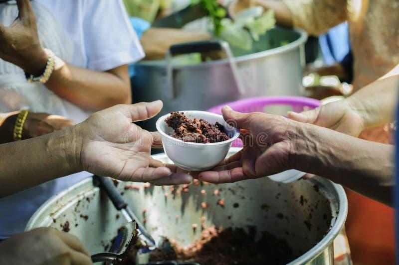 La mano ha offerto donare l'alimento da una parte dell'uomo ricco: Il concetto di divisione sociale: Gente povera che riceve alim immagine stock