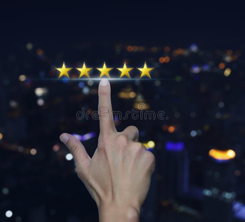 La mano hace clic en cinco estrellas amarillas para aumentar el clasificación sobre empañado foto de archivo libre de regalías