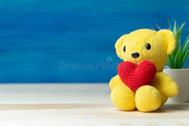 La mano hace el corazón del rojo del hilado puso en oso de peluche amarillo delante del pote blanco y de las plantas ornamentales fotografía de archivo