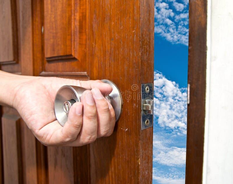 La mano humana abre una puerta en el cielo azul imagen de archivo libre de regalías