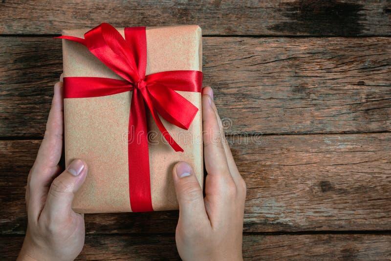 La mano humana del hombre de la prima da a actual corbata de lazo de la caja de regalo de Brown la cinta roja en vieja Feliz Navi fotografía de archivo
